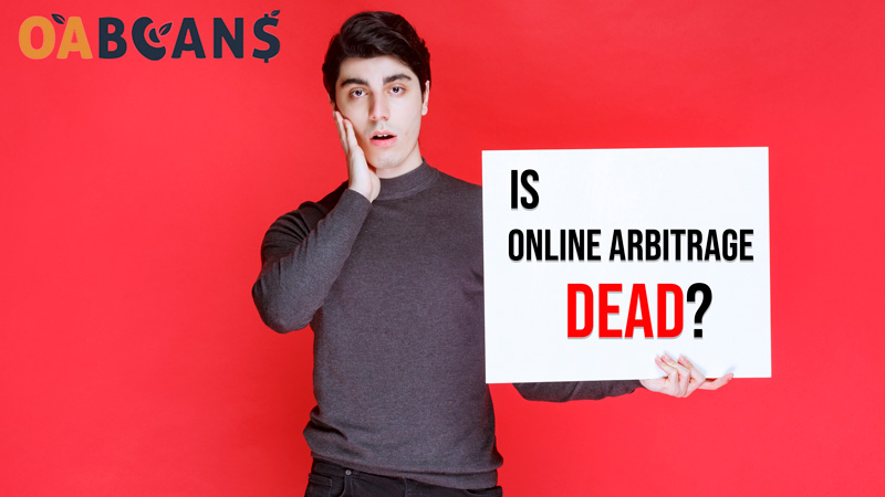 """The surprised man holds a sign that written """" is online arbitrage dead"""" on it"""