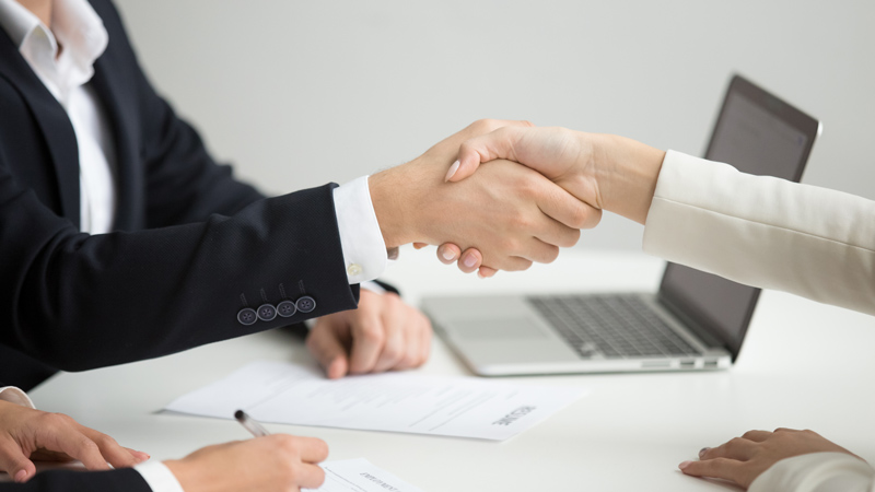 Man is shaking hand with a woman after hiring her.